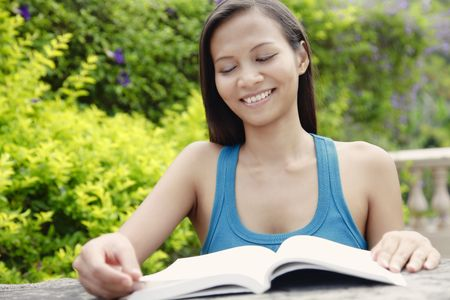 Young Asian Woman Smiling and Reading a Book in the Garden photo