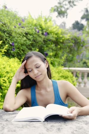 Young Asian Woman Reading a Book in the Garden