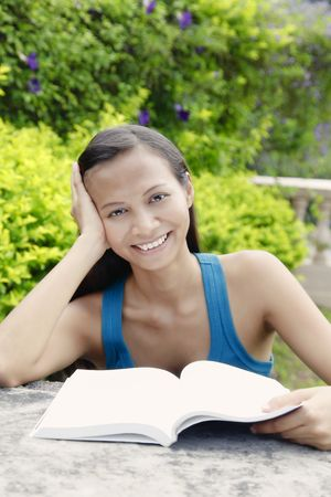 quite time: Young Asian Woman Smiling and Reading a Book in the Garden Stock Photo