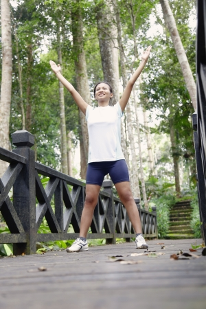 Young Asian Woman Exercising on a Wooden Bridge in the Forest
