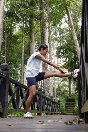 legs wide open: Young Asian Woman Exercising on a Wooden Bridge in the Forest