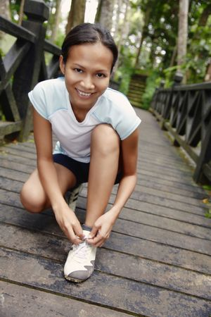 Young Asian Woman Kneeling to Tie Her Shoe Lace on a Wooden Bridge photo