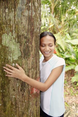 quite time: Young Asian Woman Hugging a Tree in the Forest