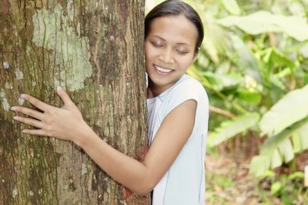 Young Asian Woman Hugging a Tree in the Forest