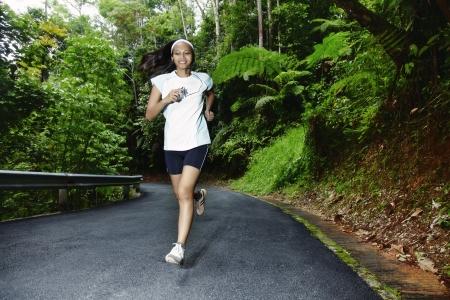 forrest: Jonge Aziatische vrouw jogging langs een smalle land Road