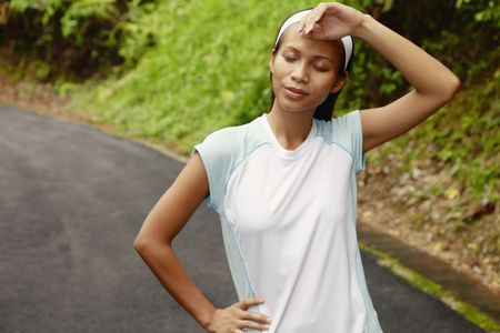 collarless: Young Asian Woman Wiping Her Brow After Exercising