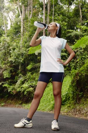 Young Asian Woman Drinking Water and Resting After Exercising photo