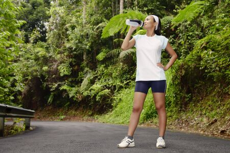 Young Asian Woman Resting After Exercising and Drinking Water Stock Photo