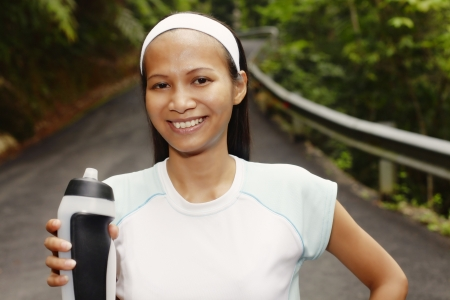 collarless: Young Asian Woman Resting After Exercising and Holding Water Bottle