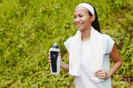 motionless: Young Asian Woman Resting After Exercising and Holding Water Bottle