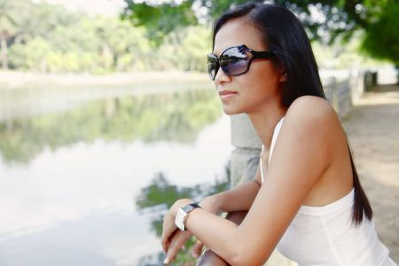 Young Asian Woman in a Reflective Mood Looking Out Towards a Lake
