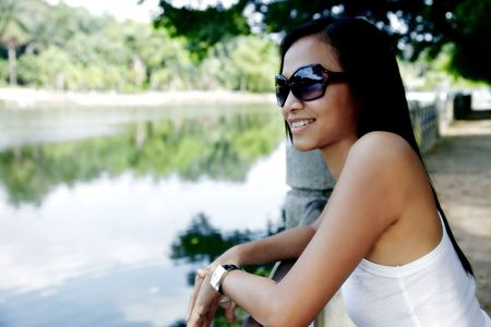 collarless: Young Asian Woman Looking Out Towards a Lake and Smiling Stock Photo