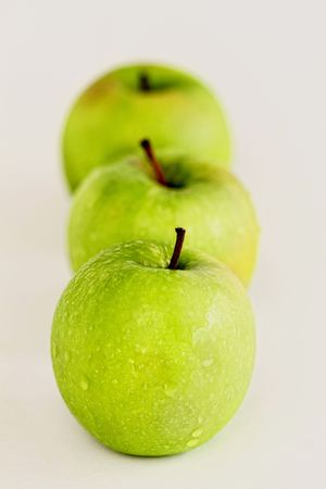 Three Fresh Green Apples in a Line Stock Photo