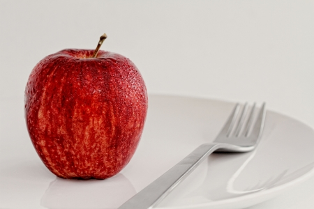 A Single Fresh Red Apple of a Plate with a Fork