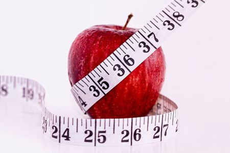 A Fresh Red Apple Encased by a Tape Measure Stock Photo