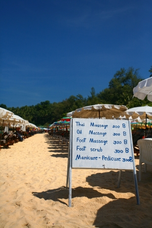 Sun Loungers and Parasols along Surin Beach, Thailand with a Sign for Massage Prices photo