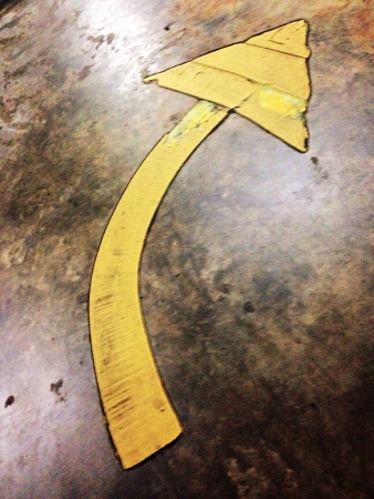 Yellow Painted Curved Arrow on Grunge Textured Surface Stock Photo