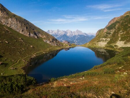 Flowing of the wild lake in Austrian Alps, epic landscape scenery, snowy mountains in back