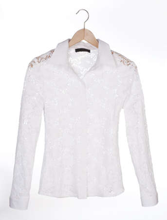 white lace blouse on a hanger