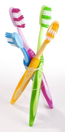 colorful toothbrushes tied together with dental floss  Stock Photo