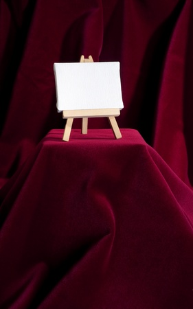 wooden easel with blank canvas on deep red velvet background