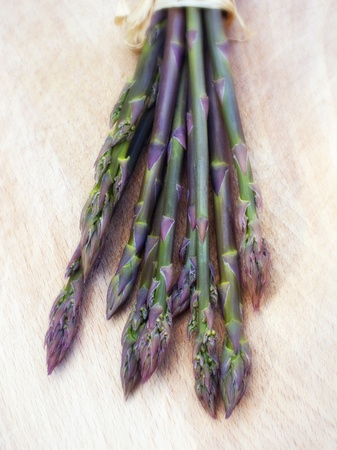 green purple asparagus on wooden cutting board
