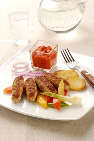 Traditional cevapcici with ajvar paste and vegetable Stock Photo