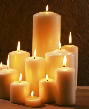 church worship: Group of burning candles at a dark background