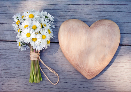 Herz aus Holz und einem Bouquet von Gänseblümchen