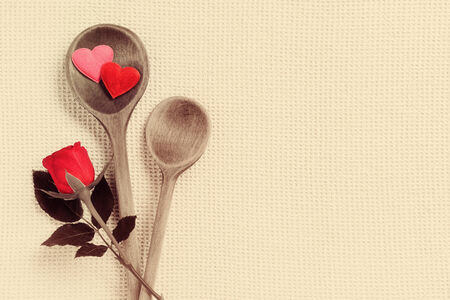 s stomach: cooking spoons and red rose on beige background