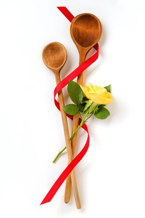 two wooden cooking spoon with yellow rose Stock Photo