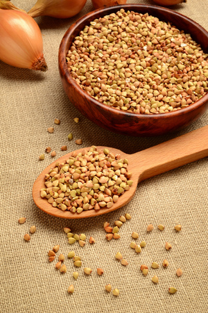 dry buckwheat grains in wooden spoon and bowl