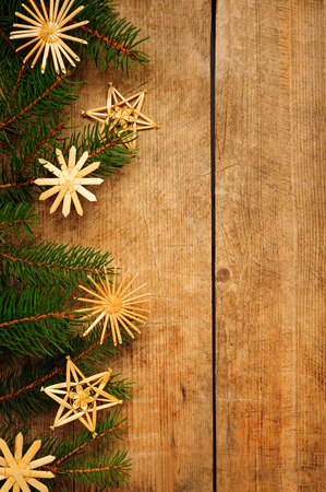 straw christmas tree stars over wooden background