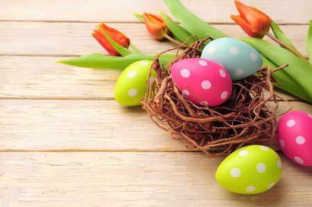 Easter basket with colored eggs over wooden background