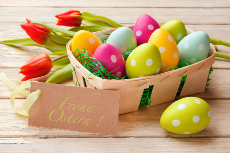 Ostern: Easter basket with colored eggs and label Frohe Ostern! (Happy Easter) Stock Photo