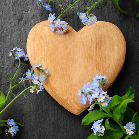 wooden heart and forget-me-not over black slate background photo