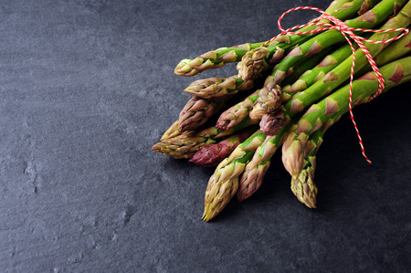green and purple vegetables: fresh green asparagus over black slater  background Stock Photo