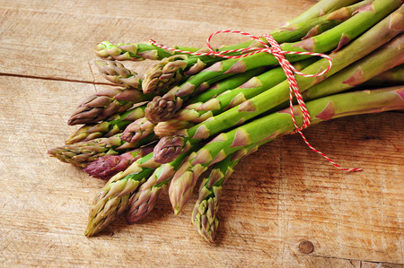 green: fresh green asparagus over wooden background