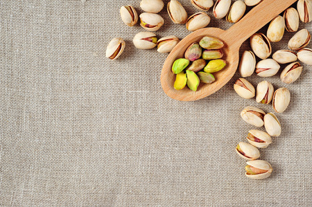 ecru: pistachios over ecru linen fabric background Stock Photo