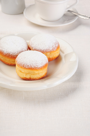 fasching: three doughnuts on white plate and coffee cup Stock Photo