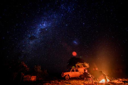 Kamperen 's nachts met vuur en sterren in het Hwange National Park, Zimbabwe.
