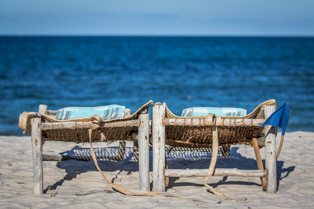 Laying beds in the sand on the beach on the Swahili Coast, Tanzania Stock Photo