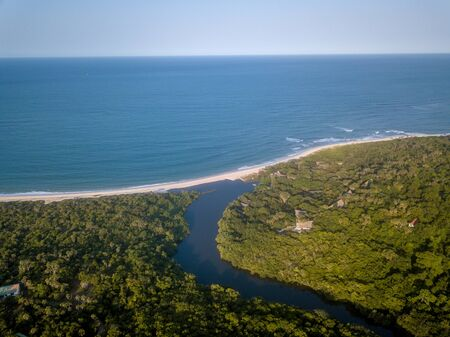 Drone picture of a lagoon in a coastal forest and the Indian ocean on the Swahili Coast, Tanzania.