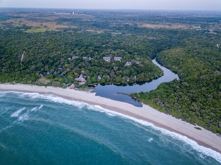 Drone picture of a hotel by a lagoon in a coastal forest on the Swahili Coast, Tanzania. Stockfoto - 134021168