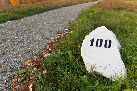 mile: Mile stone in the grass near the road, with print number hundred sign Stock Photo