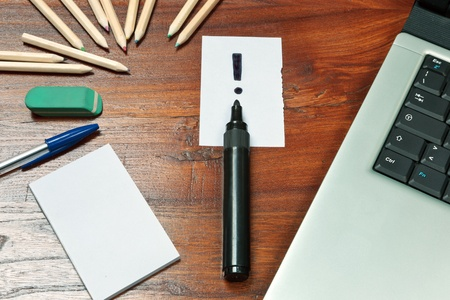 note of exclamation: Exclamation mark over a black pen on a wooden desk with computer, pen and other  paper note