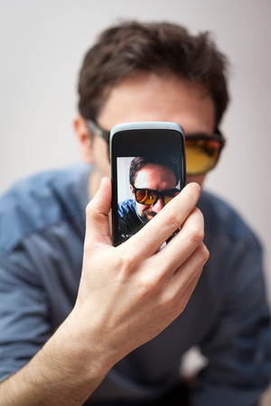 man with sun glasses take a selfie of him photo