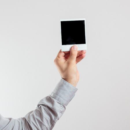 hand holding a square photo frame like polaroid