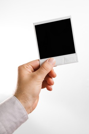 vertical composition: hand holding a square photo frame like polaroid vertical composition