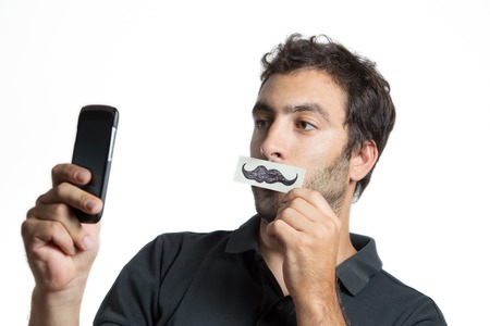 fake smile: casual man make selfie portrait with fake moustache,  close composition isolated Stock Photo